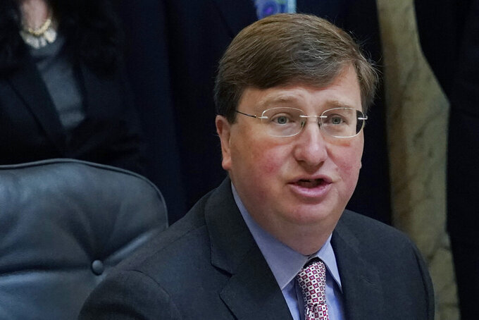 FILE - In this March 11, 2021, file photo, Mississippi Gov. Tate Reeves speaks with reporters after signing a bill at the Capitol in Jackson, Miss. A new Mississippi law will make more inmates eligible for the possibility of parole. Gov. Reeves signed Senate Bill 2795 on Thursday, April 22, 2021, and it becomes law on July 1. (AP Photo/Rogelio V. Solis, File)