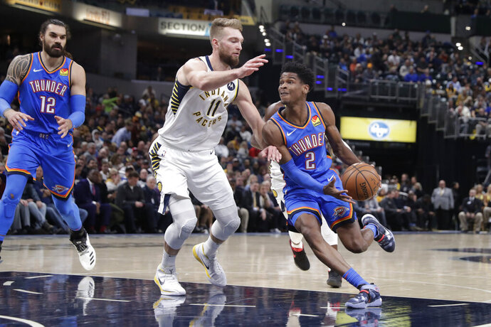 Oklahoma City Thunder guard Shai Gilgeous-Alexander (2) drives on Indiana Pacers forward Domantas Sabonis (11) during the first half of an NBA basketball game in Indianapolis, Tuesday, Nov. 12, 2019. (AP Photo/Michael Conroy)