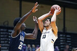 Mount St. Mary's forward Nana Opoku (22) tries to block Bryant guard Luis Hurtado (10) during the first half of an NCAA college basketball game for the Northeast Conference men's tournament championship Tuesday, March 9, 2021, in Smithfield, R.I. (AP Photo/Charles Krupa)