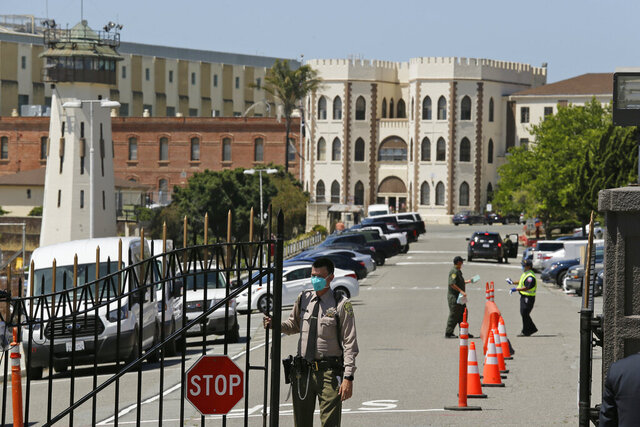 FILE - In this July 9, 2020, file photo, a correctional officer closes the main gate at San Quentin State Prison in San Quentin, Calif. California prison officials did a poor job requiring inmates and staff to wear masks to slow the spread of the coronavirus, and even
