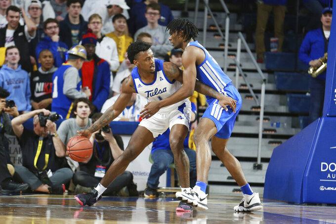 Tulsa forward Martins Igbanu (1) dribbles to the basket against Memphis forward Precious Achiuwa (55) in the first half of an NCAA college basketball game in Tulsa, Okla., Wednesday, Jan. 22, 2020. (AP Photo/Joey Johnson)