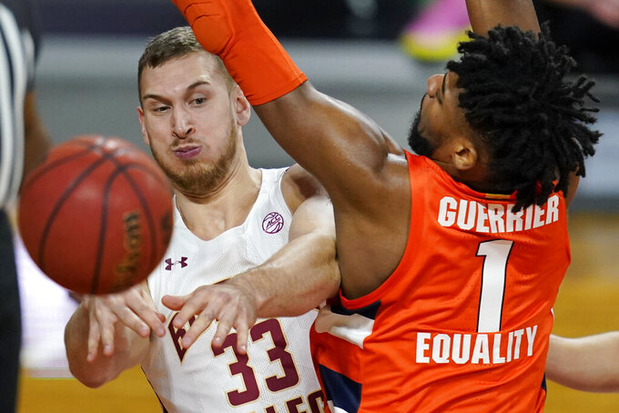 Boston College forward James Karnik (33) passes the ball as Syracuse forward Quincy Guerrier (1) defends during the first half of an NCAA college basketball game, Saturday, Dec. 12, 2020, in Boston. (AP Photo/Elise Amendola)