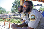 In this July 6, 2018 photo, University of Minnesota football players Jerry Gibson, right, and Winston DeLattiboudere work security guards this summer at the Como Park Zoo and Conservatory for the city of St. Paul, Minn., a few miles from the university campus. One of the Gophers coaches connected them to the opportunity. (AP Photo/Jim Mone)