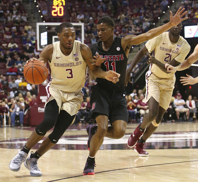 Florida State's Trent Forrest works the ball up court against North Carolina State's Markell Johnson (11) in the first half of an NCAA college basketball game Saturday, March 2, 2019, in Tallahassee, Fla. (AP Photo/Steve Cannon)
