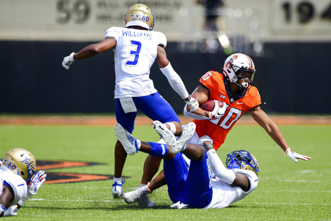 Oklahoma state Chuba Hubbard (30) is brought tackled by Tulsa defenders Cristian Williams (3) and Kenfarin Ray (1) in the second half of an NCAA college football game Saturday, Sept. 19, 2020, in Stillwater, Okla. (AP Photo/Brody Schmidt)
