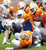Chattanooga running back Ailym Ford (32) is tackled by Tennessee linebacker Henry To'o To'o (11), defensive back Nigel Warrior (18), linebacker Quavaris Crouch (27) and linebacker Jeremy Banks (33) in the first half of an NCAA college football game Saturday, Sept. 14, 2019, in Knoxville, Tenn. (AP Photo/Wade Payne)