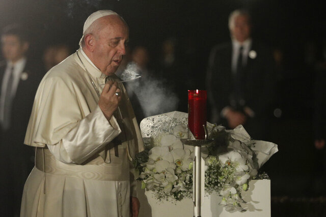 Pope Francis blows out after lighting a candle as he visits Hiroshima Peace Memorial Park in Hiroshima, western Japan, Sunday, Nov. 24, 2019. (AP Photo/Gregorio Borgia)