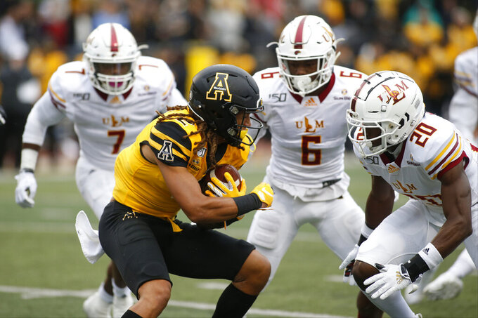 Appalachian State wide receiver Corey Xavier Sutton (2) runs for a first down against Louisiana Monroe  safety Keilos Swinney (6) and cornerback Josh Newton (20) during the first half of an NCAA college football game Saturday, Oct. 19, 2019, in Boone, NC. (AP Photo/Brian Blanco)