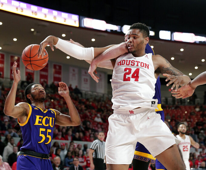 Houston forward Breaon Brady (24) is fouled on a rebound from behind by East Carolina forward Dimitrije Spasojevic, back, as East Carolina guard Shawn Williams (55) looks on during the first half of an NCAA college basketball game Wednesday, Jan. 23, 2019, in Houston. (AP Photo/Michael Wyke)