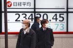 People walk by an electronic stock board of a securities firm in Tokyo, Monday, Jan. 27, 2020. Shares tumbled Monday in the few Asian markets open as China announced sharp increases in the number of people affected in an outbreak of a potentially deadly virus. (AP Photo/Koji Sasahara)