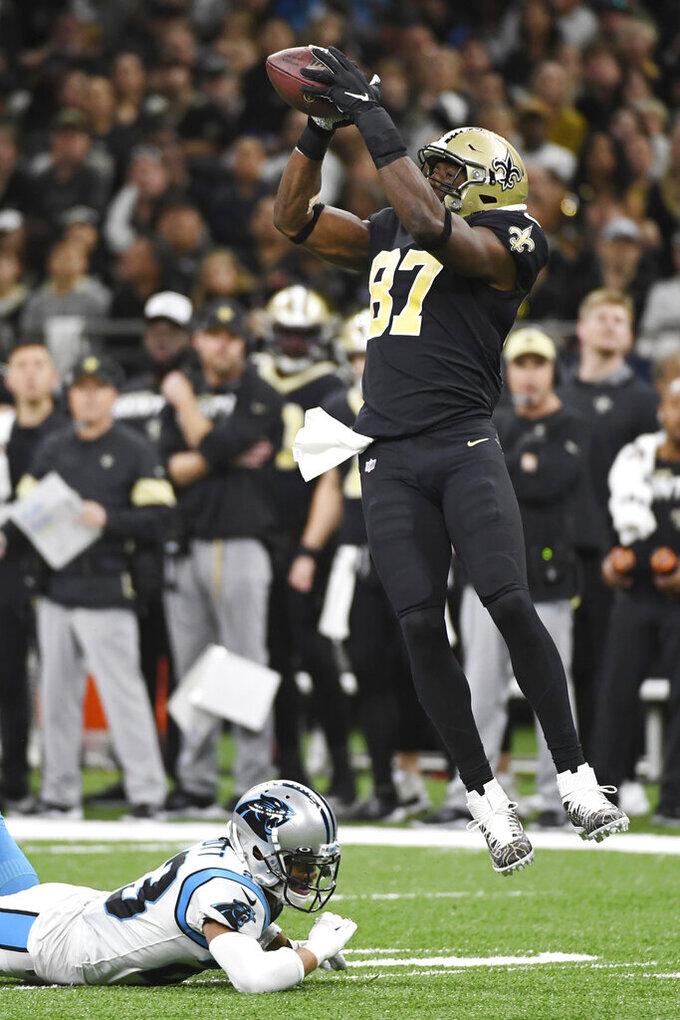 New Orleans Saints tight end Jared Cook (87) grabs the ball, as Carolina Panthers cornerback Javien Elliott (23), is late with the tackle, during the first half at an NFL football game, Sunday, Nov. 24, 2019, in New Orleans. (AP Photo/Bill Feig)