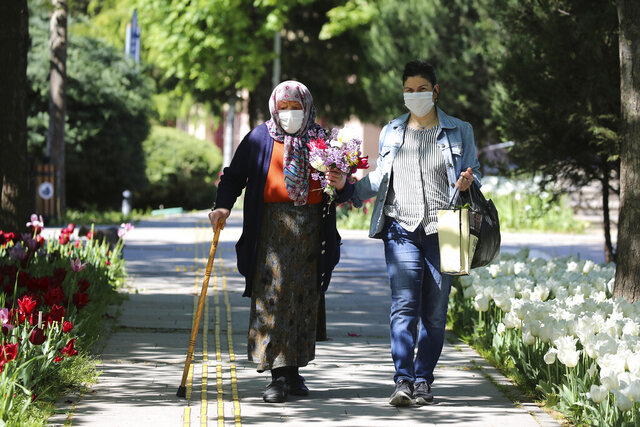 An elderly woman wearing a face mask to protect against coronavirus, holds flowers she have received on the Mother's Day in a public garden during a two-day curfew declared by the government in an attempt to control the spread of coronavirus, in Ankara, Turkey, Sunday, May 10, 2020. Only senior people over 65 have been allowed to go out for four hours on Sunday. (AP Photo/Burhan Ozbilici)
