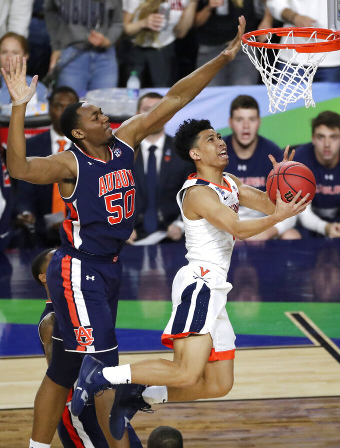 Virginia guard Kihei Clark drives to the basket past Auburn center Austin Wiley, left, during the first half in the semifinals of the Final Four NCAA college basketball tournament, Saturday, April 6, 2019, in Minneapolis. (AP Photo/Matt York)