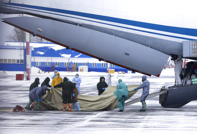 A group of medical personnel prepare to meet 80 people, accompanied by medical specialists, carried by a Russian military plane at an airport outside Tyumen, Russia, Wednesday, Feb. 5, 2020. Russia has evacuated 144 people, Russians and nationals of Belarus, Ukraine and Armenia, from the epicenter of the coronavirus outbreak in Wuhan, China, on Wednesday. All evacuees will be quarantined for two weeks in a sanatorium in the Tyumen region in western Siberia, government officials said. (AP Photo/Maxim Slutsky)