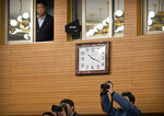 An official watches as journalists take photos during a press conference with Chinese Foreign Minister Wang Yi on the sidelines of the annual meeting of China's National People's Congress (NPC) in Beijing, Friday, March 8, 2019. The U.S.-North Korea summit in Vietnam last week was an