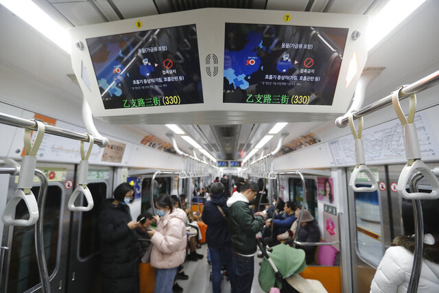 FILE - This Jan. 29, 2020, file photo shows screens warning about a new coronavirus in a subway train in Seoul, South Korea. The dangerous virus spreading through China threatens a wide range of industries with global ties to the world's second largest economy. Chinese authorities have cut off access to Wuhan, where the virus originated, and 16 other cities to prevent further spread of the virus, affecting more than 50 million people. (AP Photo/Ahn Young-joon, File)