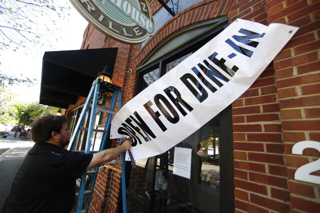 FILE - In this April 27, 2020, file photo, Jason Godbey hangs a banner over the entrance of Madison Chop House Grille as they prepare to shift from take out only to dine-in service in Madison, Ga. Gov. Strong concern about a second wave of coronavirus infections is reinforcing widespread opposition among Americans to reopening public places, a new polls finds, even as many state leaders step up efforts to return to life before the pandemic. AP Photo/John Bazemore, File)