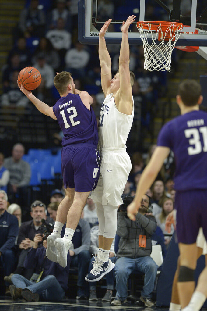 Northwestern's Pat Spencer (12) puts up a left-handed shot as Penn State's John Harrar defends during first half action in an NCAA college basketball game, Saturday, Feb. 15, 2020, in State College, Pa. (AP Photo/Gary M. Baranec)