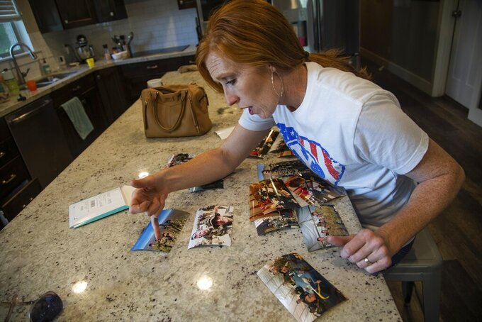 """In this May 29, 2020 photo,  Jennie Taylor, looks through printed pictures of her husband Maj. Brent Taylor and his time in Afghanistan in her North Ogden, Utah home.  Seeing the collapse of the government of Afghanistan following the departure of U.S. forces from the country, seeing the Taliban take control, is tough for Taylor. """"It's heartbreaking. I don't know if there's another word for it,"""" said the North Ogden woman. Her late husband, Brent Taylor, a major in the Utah Army National Guard, died in late 2018 while on a tour of duty in Afghanistan, so the recent turn of events hits close to home. (Ben Dorger/Standard-Examiner via AP)"""