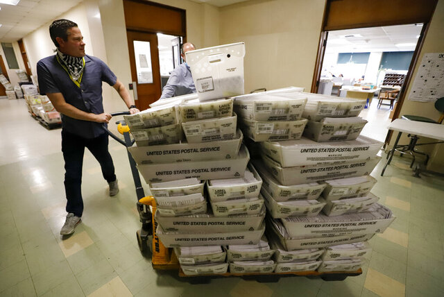 Chet Harhut, deputy manager, of the Allegheny County Division of Elections, wheels a dolly loaded with mail-in ballots, at the division of elections offices in downtown Pittsburgh Wednesday, May 27, 2020. The once-delayed June 2, Pennsylvania primary will feature legislative and congressional races, a first run for some new paper-record voting systems and the inaugural use of newly legalized mail-in ballots. (AP Photo/Gene J. Puskar)