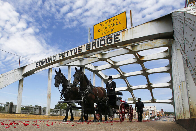 The casket of U.S. Rep. John Lewis, D-Ga., crosses the Edmund Pettus Bridge by horse-drawn carriage during a memorial service for the civil rights activist in Selma, Ala., on Sunday, July 26, 2020. Lewis, who carried the struggle against racial discrimination from Southern battlegrounds of the 1960s to the halls of Congress, died Friday, July 17, 2020. (AP Photo/John Bazemore)
