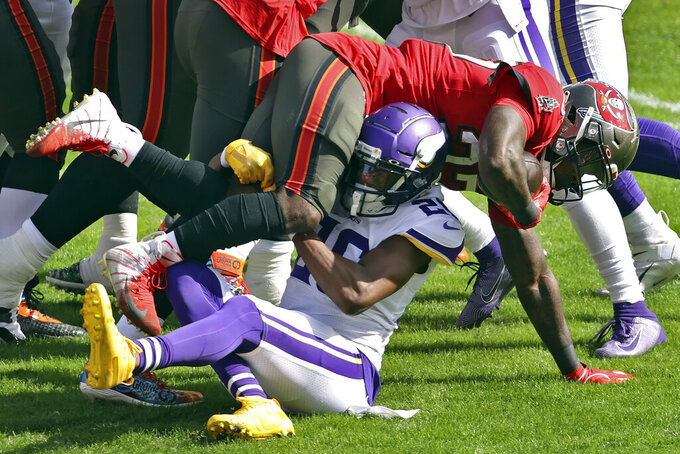Minnesota Vikings defensive back Chris Jones (26) upends Tampa Bay Buccaneers running back Ronald Jones II (27) during the first half of an NFL football game Sunday, Dec. 13, 2020, in Tampa, Fla. (AP Photo/Mark LoMoglio)