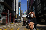 A woman wearing face mask walks on a down town street in Hong Kong Wednesday, Feb. 26, 2020. COVID-19 viral illness has sickened tens of thousands of people in China since December. (AP Photo/Vincent Yu)