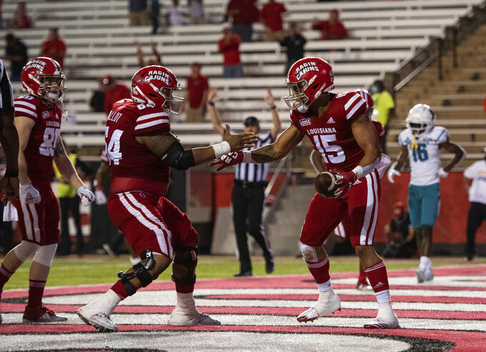 Louisiana-Lafayette running back Elijah Mitchell (15) and offensive lineman Shane Vallot (64) celebrate a touchdown by Mitchell during the second half of an NCAA college football game against Coastal Carolina in Lafayette, La., Wednesday, Oct. 14, 2020. (AP Photo/Paul Kieu)