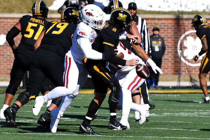 Missouri quarterback Connor Bazelak, right, fumbles as he is hit by Arkansas defensive lineman Julius Coates during the first half of an NCAA college football game Saturday, Dec. 5, 2020, in Columbia, Mo. (AP Photo/L.G. Patterson)