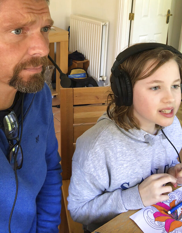 Cricket announcer Mark Church takes a selfie photo with his daughter Isabelle, in Cardiff, Wales, Sunday March 22, 2020, while they record one of the video commentaries.  Church has taken to doing short commentaries of some of the sport's major moments alongside his 10-year old daughter at their home or in the car, filling the void in his working life caused by the coronavirus outbreak.  The highly contagious COVID-19 coronavirus can cause mild symptoms, but for some it can cause severe illness including pneumonia. (Mark Church via AP)