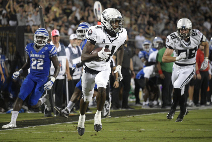 Central Florida wide receiver Ryan O'Keefe (4) runs into the end zone with a touchdown reception, as Memphis defensive back Tyrez Lindsey (22) watches during the first half of an NCAA college football game Friday, Oct. 22, 2021, in Orlando, Fla. (Phelan M. Ebenhack/Orlando Sentinel via AP)