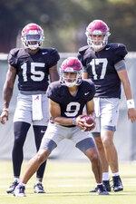 Alabama quarterback Bryce Young (9) runs a drill with fellow quarterbacks Jalen Milroe (15) and Paul Tyson (17) watching at NCAA college fall camp football practice, Monday, Aug. 9, 2021, in Tuscaloosa, Ala. (AP Photo/Vasha Hunt)