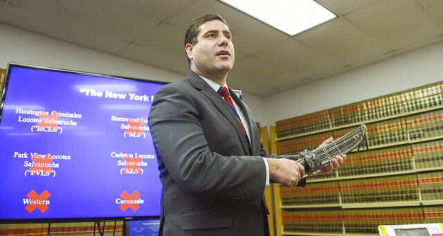 Suffolk County District Attorney Timothy Sini holds a machete while announcing an indictment of nearly 100 MS-13 gang members and associates during a news conference at Suffolk County Court in Riverhead, N.Y., Friday, Dec. 20, 2019. The two-year investigation by state and federal authorities thwarted more than a half-dozen murder plots, Sini said, and also provided authorities insights into the gang's structure and recruiting patterns. (James Carbone/Newsday via AP)