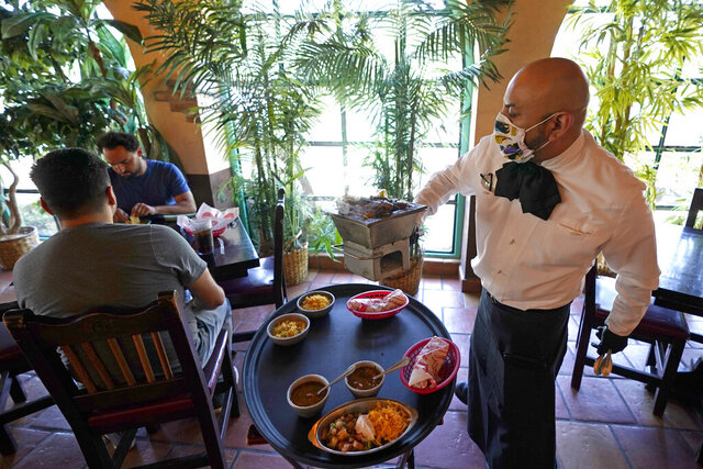 Waiter Marcos Huerta, right, serves a grill of fajitas at El Tiempo Cantina Friday, May 1, 2020, in Houston. The restaurant reopened their dining room for table service, with limited capacity, Friday. Texas' stay-at-home orders due to the COVID-19 pandemic have expired and Texas Gov. Greg Abbott has eased restrictions on many businesses that have now opened. (AP Photo/David J. Phillip)