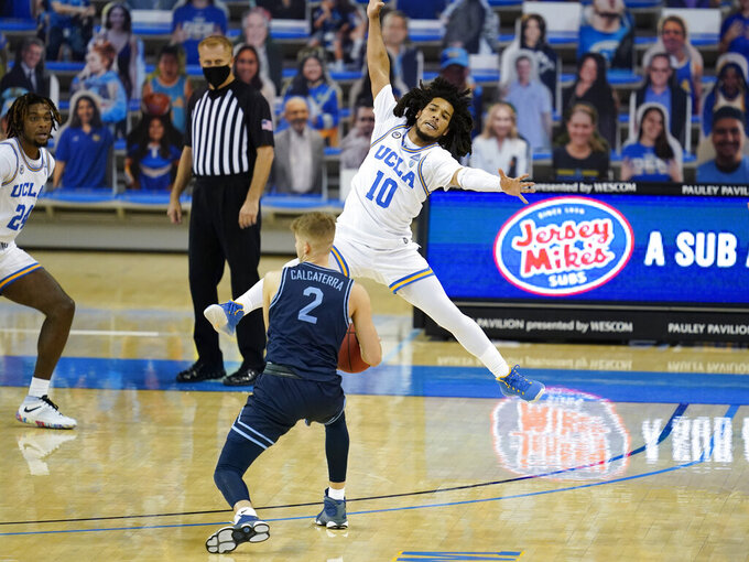 UCLA guard Tyger Campbell (10) defends against San Diego guard Joey Calcaterra (2) during the first half of an NCAA college basketball game Wednesday, Dec. 9, 2020, in Los Angeles. (AP Photo/Ashley Landis)