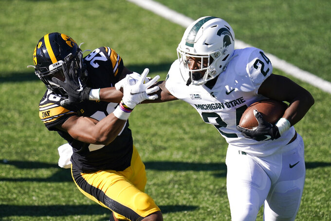 Michigan State running back Elijah Collins (24) runs from Iowa defensive back Kaevon Merriweather, left, during the first half of an NCAA college football game, Saturday, Nov. 7, 2020, in Iowa City, Iowa. (AP Photo/Charlie Neibergall)