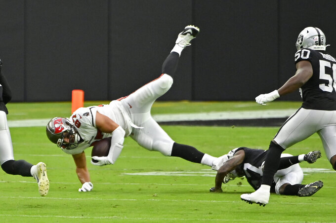 Las Vegas Raiders cornerback Trayvon Mullen (27) tackles Tampa Bay Buccaneers tight end Rob Gronkowski (87) during the first half of an NFL football game, Sunday, Oct. 25, 2020, in Las Vegas. (AP Photo/David Becker)