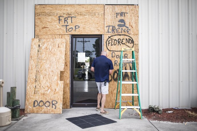 Terry Crabtree finishes boarding up the entrance to Downeast Marine in Otway, N.C. as Tropical Storm Isaias approaches on Monday, Aug. 3, 2020. (Julia Wall/The News & Observer via AP)