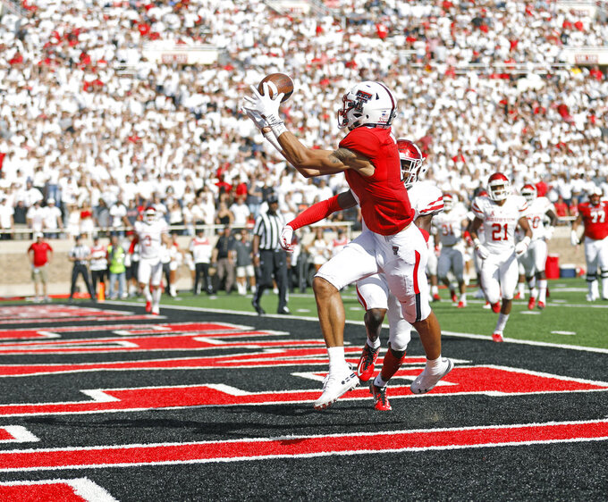 Texas Tech's Antoine Wesley (4) catches a pass in the end zone for a touchdown in front of Houston's Isaiah Johnson (14) during an NCAA college football game Saturday, Sept. 15, 2018, in Lubbock, Texas. (Brad Tollefson/Lubbock Avalanche-Journal via AP)