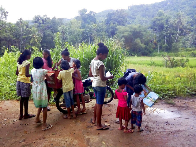 "Children look to borrow books from a mobile library run on a motorbike by Mahinda Dasanayaka, in a village in Kegalle district, about 85 kilometers (53 miles) northeast of Sri Lanka's capital, Colombo, July 26, 20019. Having witnessed the hardships faced by children in rural areas whose villages have no library facilities, Dasanayaka got the idea for his library on wheels called ""Book and Me."