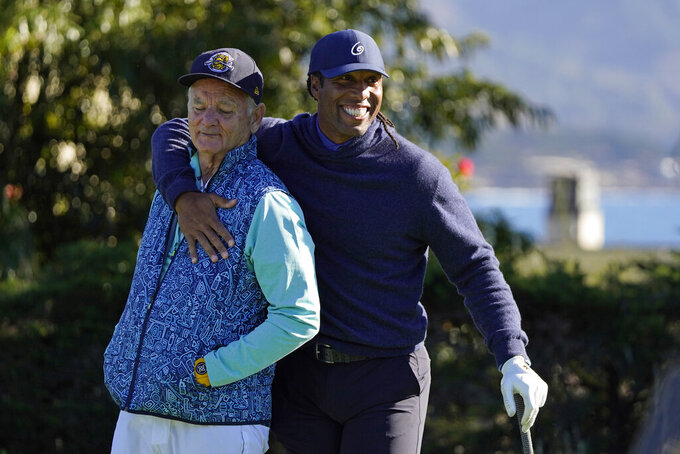 Bill Murray, left, is embraced by Larry Fitzgerald on the first tee during the charity challenge event of the AT&T Pebble Beach Pro-Am golf tournament Wednesday, Feb. 10, 2021, in Pebble Beach, Calif. (AP Photo/Eric Risberg)