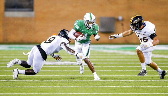 North Texas wide receiver Jaelon Darden (1) carries the ball as Southern Mississippi defensive back Malik Shorts (9) and linebacker Averie Habas (46) defend during the first half of an NCAA college football game Saturday, Oct. 3, 2020, in Denton, Texas. (AP Photo/Brandon Wade)