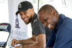 CORRECTS TO PRESIDENT, NOT INTERIM PRESIDENT AS ORIGINALLY SENT - Golden State Warriors guard Stephen Curry, left, and Howard University president Wayne Frederick laugh before a news conference at Langston Golf Course in Washington, Monday, Aug. 19, 2019, where Curry announced that he would be sponsoring men's and women's golf teams at Howard University. (AP Photo/Andrew Harnik)