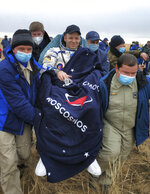 In this photo released by Rosaviatsiya, rescue team members carry Roscosmos' cosmonaut Ivan Vagner shortly after the landing near town of Dzhezkazgan, Kazakhstan, Thursday, Oct. 22, 2020. A trio of space travelers safely returned to Earth on Thursday after a six-month mission on the International Space Station. The Soyuz MS-16 capsule carrying NASA astronaut Chris Cassidy, and Roscosmos' Anatoly Ivanishin and Ivan Vagner landed on the steppes of Kazakhstan southeast of the town of Dzhezkazgan on Thursday. (Rosaviatsiya via AP)