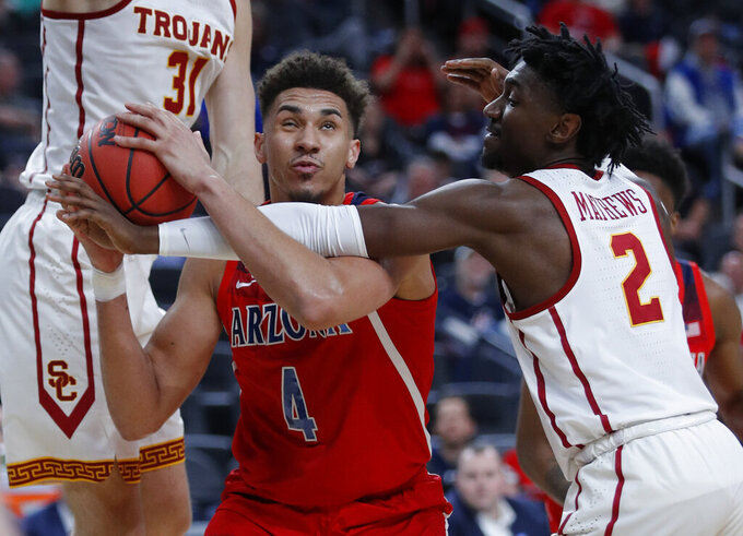 Southern California's Jonah Mathews, right, reaches in against Arizona's Chase Jeter (4) during the second half of an NCAA college basketball game in the first round of the Pac-12 men's tournament Wednesday, March 13, 2019, in Las Vegas. (AP Photo/John Locher)