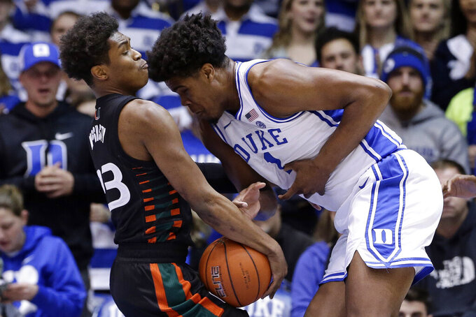 Miami guard Kameron McGusty, left, and Duke center Vernon Carey Jr. (1) struggle for possession of the ball during the first half of an NCAA college basketball game in Durham, N.C., Tuesday, Jan. 21, 2020. (AP Photo/Gerry Broome)