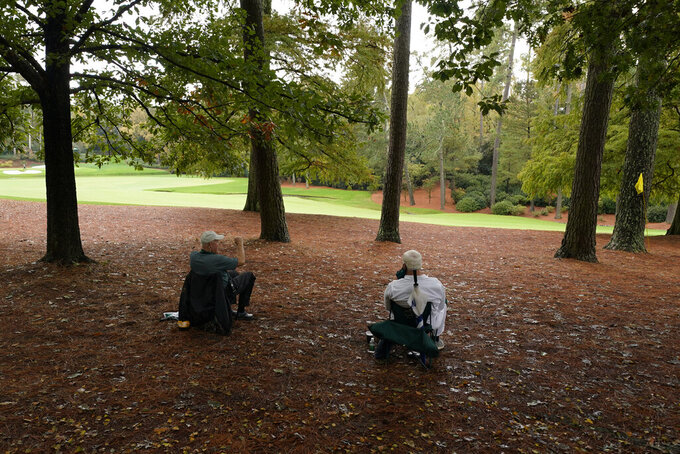 Course marshalls wait for golfers on the 13th hole during a practice round for the Masters golf tournament Wednesday, Nov. 11, 2020, in Augusta, Ga. (AP Photo/Charlie Riedel)