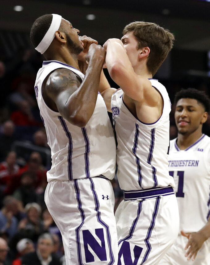 Northwestern center Dererk Pardon, left, celebrates with forward Miller Kopp after scoring a basket against Ohio State during the second half of an NCAA college basketball game Wednesday, March 6, 2019, in Evanston, Ill. (AP Photo/Nam Y. Huh)