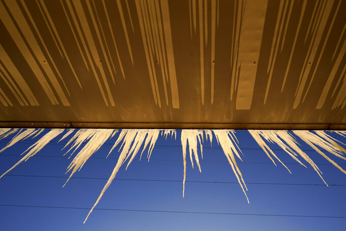 Icicles hang from a building Saturday, Feb. 13, 2021, in North Kansas City, Mo. A cold streak continues across the region with temperatures expected to drop to -13 degrees Fahrenheit by by Monday.(AP Photo/Charlie Riedel)