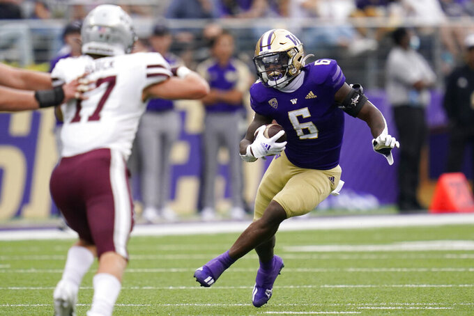 Washington's Richard Newton (6) carries the ball as Montana's Robby Hauck defends in the first half of an NCAA college football game Saturday, Sept. 4, 2021, in Seattle. (AP Photo/Elaine Thompson)